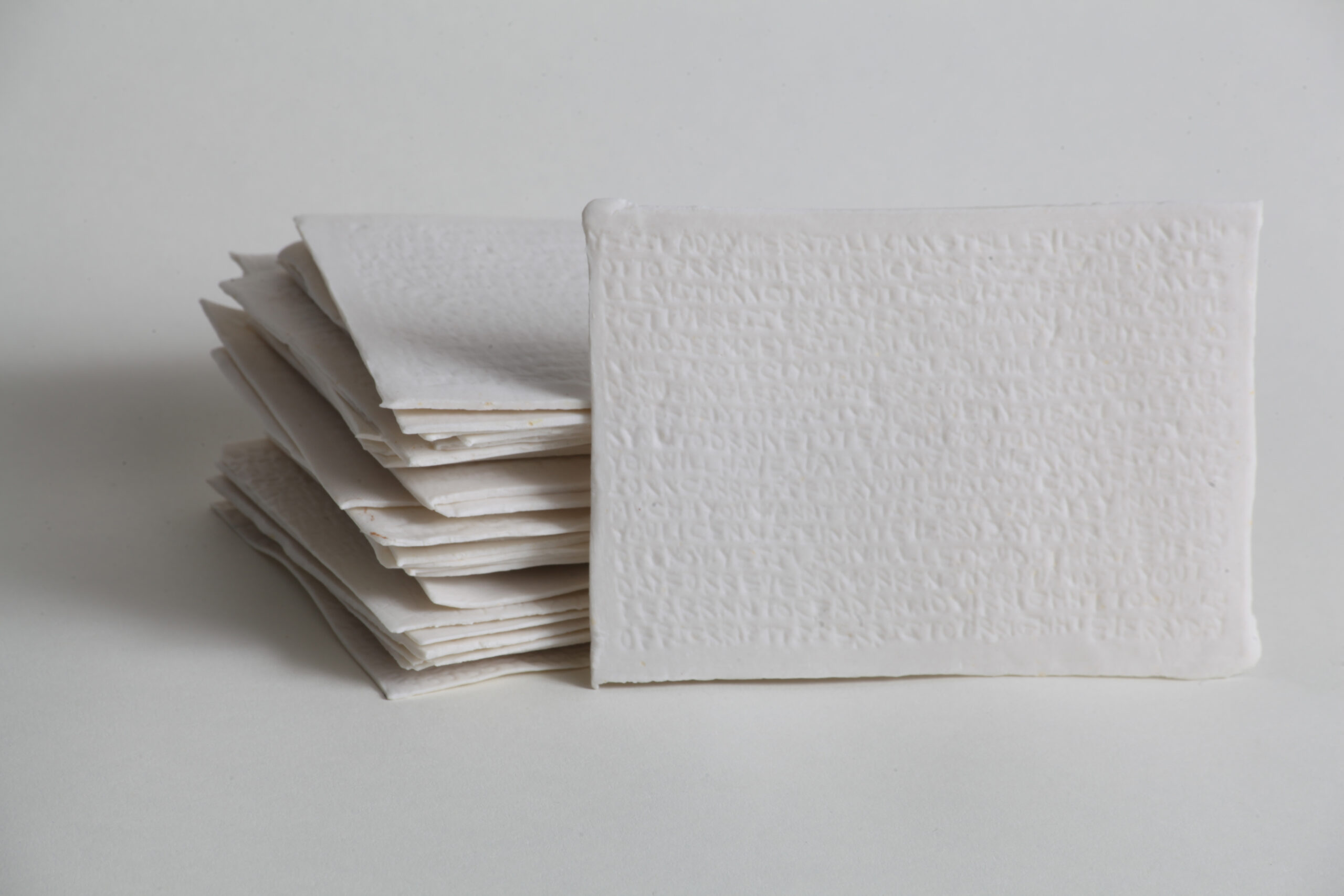 A stack of white porcelain postcards photographed on a white background.