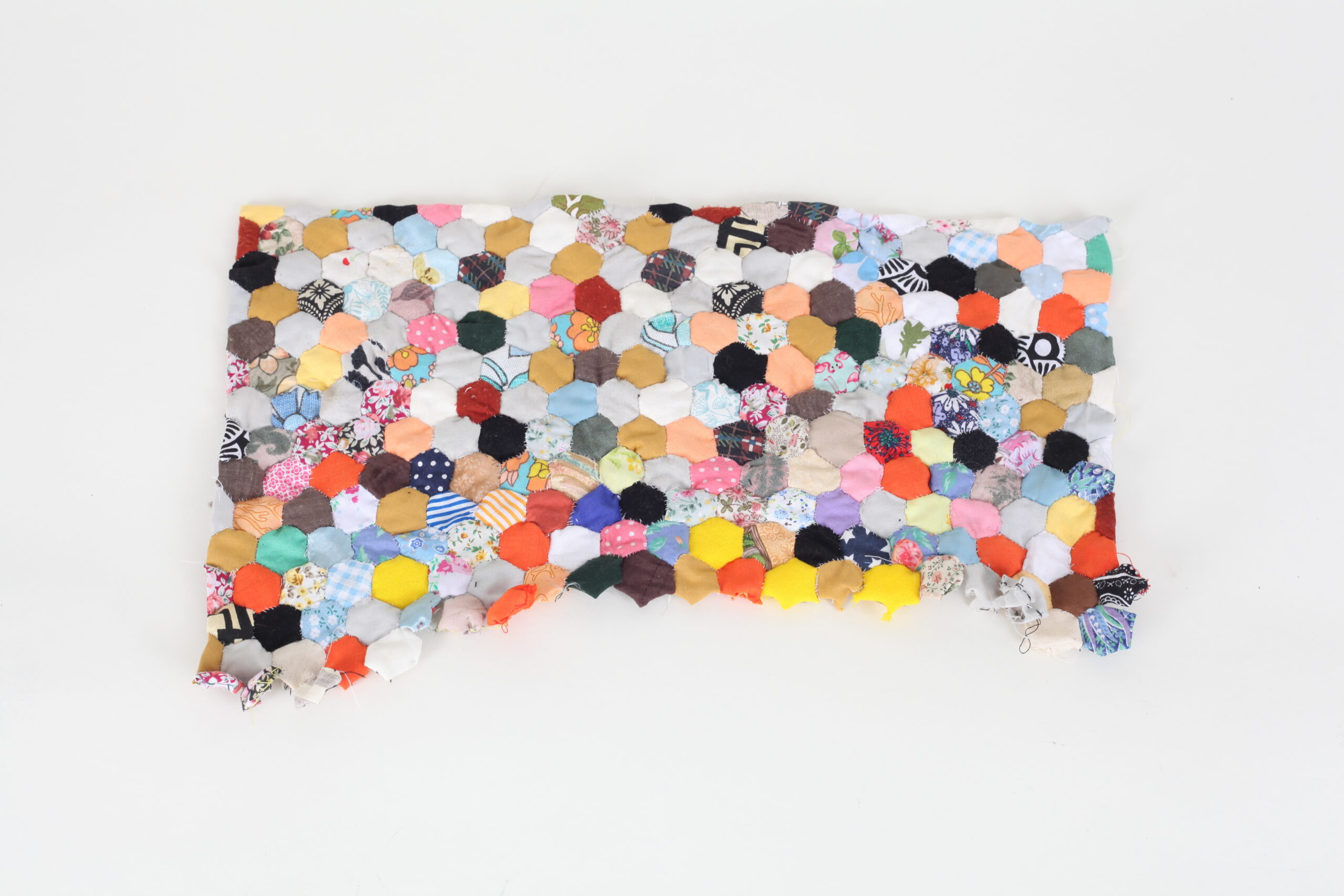 Patch work embroidery made from hundreds of colourful pieces of material.