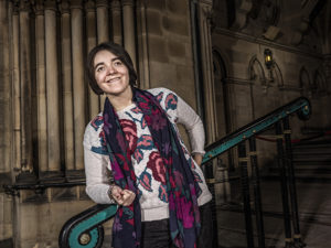 Amber leaning against a banister smiling at the camera.