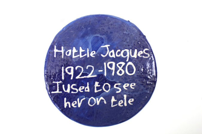 Horace has been working on an ever-expanding series of ceramic 'blue plaques' commemorating people who have been important in his life. They include comedians and actors from Carry-On films and soaps, as well as less well known people like Horace's favourite taxi driver. (Image: 'Hattie Jacques', ceramic, 2019)