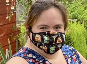Head and shoulder shot of Amy in her garden wearing a mask printed with her cocktail design