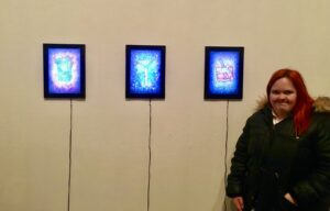 Amy stood in front of her art work 'Cocktails' displayed on 3 iPads.