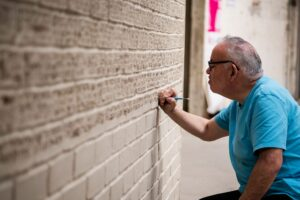 Barry inscribing the ceramic bricks of a large wall, some of which are on show in 50 windows of creativity
