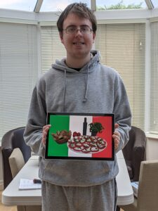 Michael holding a tablet with his prizewinning picture of Italian food with the Italian flag as a background