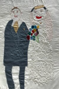 An embroidered image of Roy and Hayley Cropper from Coronation Street in their wedding outfits.
