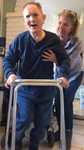 Man using a walking frame with a carer supporting him.