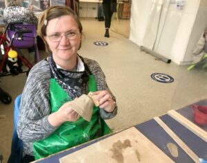 Louise is sat a table wearing a green apron. She is holding some clay she is working on and smiling.