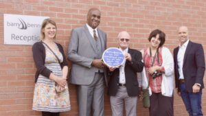 A row of 5 people in front of brick wall, Amanda, Horace, Barry, Amber and Anthony. Horace is presenting his blue plaque.