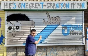 Justin stood in front of the design he has painted on the Partisan shutter.